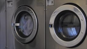 Washing machine launderette laundromat. Video of clothes spinning around in washing machine at launderette laundromat shop stock footage
