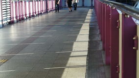 Video commuters, people walking on train station bridge with railing and sunlight. abstract transportation. Commuters, people walking on train station bridge stock video footage