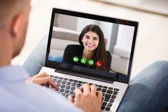 Video comunicazione dell'uomo con la sua moglie immagine stock