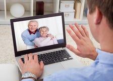 Video comunicazione dell'uomo sul computer portatile Fotografie Stock
