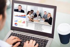 Video comunicazione della donna di affari con il computer portatile Fotografia Stock