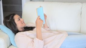 Video of concentrated woman reading a novel. On a sofa stock footage