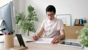 Concentrated young business woman working on desk in the office stock video footage