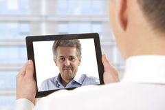 Video conference. Cropped image of businessman attending video conference with colleague on digital tablet Stock Photos