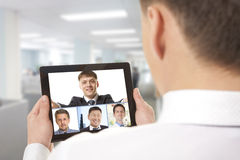 Video conference. Cropped image of team businessman attending video conference with colleague on digital tablet Stock Images
