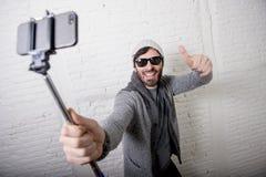 Video d'avanguardia del selfie della registrazione del bastone della tenuta dell'uomo di blogger dei giovani pantaloni a vita bas fotografie stock libere da diritti