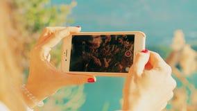 Video del paesaggio della fucilazione della giovane donna con il suo smartphone sulla riva del lago Sparato sulla macchina fotogr video d archivio