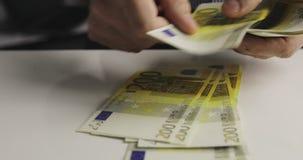 Video del primo piano delle mani dell'uomo che contano molte duecento fatture dell'euro archivi video