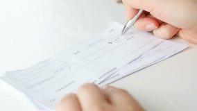 Video del primo piano 4k della giovane donna che firma 1000 dollari di assegno bancario con la penna video d archivio