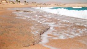 video del primo piano del movimento lento 4k di grandi onde del mare che si rompono sulla spiaggia sabbiosa archivi video