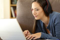 Video del watchng della ragazza con il computer portatile e le cuffie Immagine Stock