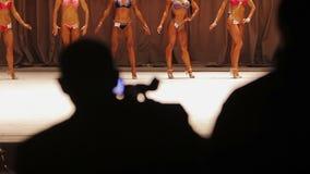 Video della registrazione della siluetta del cineoperatore del concorso di bellezza, modelli che posano in scena video d archivio