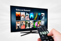 Video on demand VOD service on smart TV. Remote control in hand royalty free stock photos
