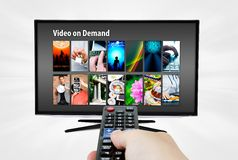 Video on demand VOD service on smart TV. Remote control in hand stock photo