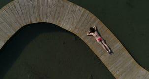 Video der Frau im Badeanzug ein Sonnenbad nehmend auf dem Pier Weibliche Entspannung auf Ferien stock video