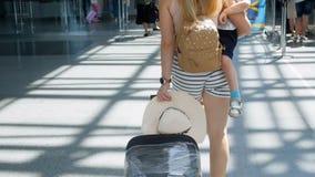 Video der hinteren Ansicht der jungen Mutter mit dem Kleinkindsohn, der Koffer auf Rädern gehend in Flughafenabfertigungsgebäude  stock footage