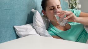 Video der Nahaufnahme 4k der jungen Frau leiden unter dem Hauptschmerz, der im Bett und in trinkendem aspirin im Glas liegt stock video footage