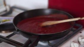 Video des Kochens der Tomatensauce in einer Wanne mit Öl, Knoblauch und schwarzem Pfeffer stock video footage