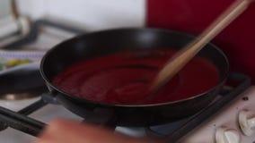 Video des Kochens der Tomatensauce in einer Wanne mit Öl, Knoblauch und schwarzem Pfeffer stock footage