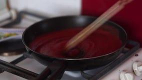 Video des Kochens der Tomatensauce in einer Wanne mit Öl, Knoblauch und schwarzem Pfeffer stock video