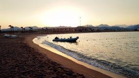Video des Schattenbildes 4k des aufblasbaren Bootes mit Motor auf Wellen des ruhigen Sees bei Sonnenuntergang stock video footage