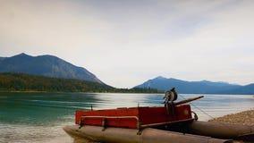 Video di lasso di tempo Vista sollevata sopra la piccola barca sulla costa della ghiaia, specchio in acqua del lago della montagn archivi video