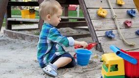 Video di movimento lento dei 2 anni svegli del bambino della sabbia di scavatura del ragazzo sul campo da giuoco al parco video d archivio