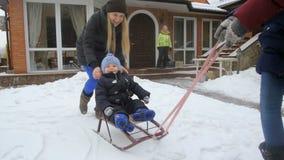 Video di movimento lento del neonato di guida della famiglia sulle slitte al cortile della casa video d archivio