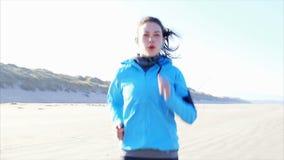 Video di movimento lento della donna risoluta che pareggia sulla spiaggia archivi video