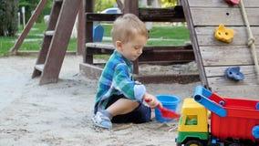 Video di movimento lento della placcatura sorridente sveglia del ragazzo e sabbia di scavatura in sabbiera con la pala di plastic stock footage