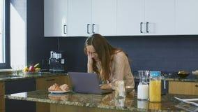 Video di sorveglianza della donna di affari in cucina Persona sorpresa che esamina computer portatile archivi video