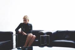 Video di sorveglianza della giovane donna alla moda sul telefono cellulare mentre sedendosi contro il fondo bianco della parete c Fotografia Stock Libera da Diritti