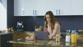 Video di sorveglianza spaventato della donna sul computer Donna di affari che si domanda nella nuova cucina video d archivio