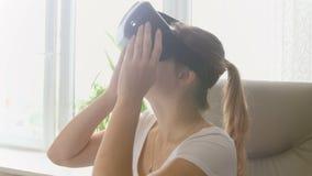 Video di sorveglianza stupito della giovane donna in cuffia avricolare di realtà virtuale e guardare intorno a se stessa Metraggi stock footage