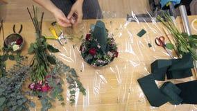 Video di vista superiore di un fiorista che crea una disposizione dei fiori fresca stock footage