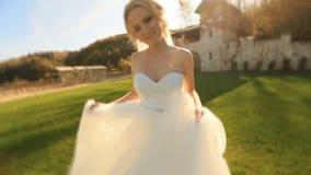 Video dinamico di bella bionda in vestito bianco sul cortile medievale del castello archivi video