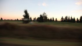 Golf Course Drive by. Video driving by a golf course at sunset stock footage