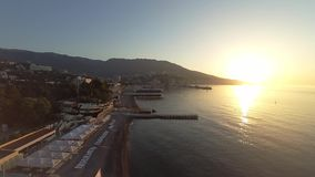 Video from drone. Summer 2017 in the Crimea. Fly under the Black sea at sunset. Beach, docks and mountains. No people stock video footage