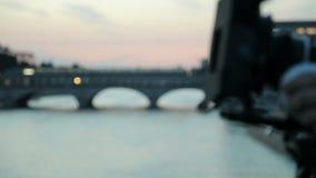 Video-dslr Kamera, die auf Schieber mit Fluss und Zug im Hintergrund voranbringt hinter den Kulissen Videoproduktion stock video