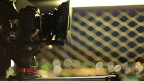 Video-dslr Kamera, die auf Schieber mit schönen Lichtern im Hintergrund voranbringt hinter den Kulissen Videoproduktion stock video