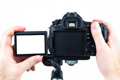 Video DSLR on Tripod. A person reviewing photos or video clips from a DSLR video camera supported on a tripod on a white background Royalty Free Stock Photos