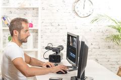 Video editor. With computer and professionnal video camera stock photo