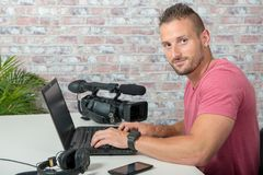 Video editor with laptop and professional video camera. A video editor with laptop and professional video camera royalty free stock image