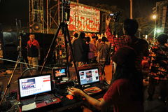Video Editor. A video editor operates an editing system during a large red-shirt rally on the Royal Plaza on January 29, 2013 in Bangkok, Thailand stock photo