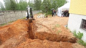 Video excavator digging a trench in the ground stock video footage