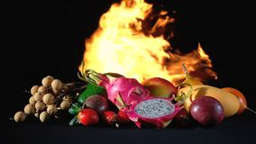Video exotic fruits in the fire on black background