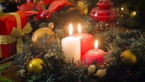 Video för Closeup 4k av kameran som fortskrider brännande stearinljus i traditionell julkrans stock video