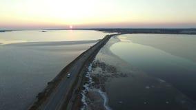 video för sammanställning 4K Flyg över vägen i den djupfrysta sjön i tidig vår på solnedgången, flyg- sikt lager videofilmer