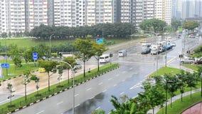 Video för Tid schackningsperiod av bilar och trafik i Singapore under en regnig dag som visar träd och HDB-byggnader stock video