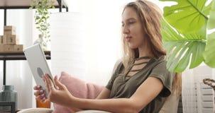 Video för tonårs- flicka som pratar genom att använda den digitala minnestavlan på soffan arkivfilmer